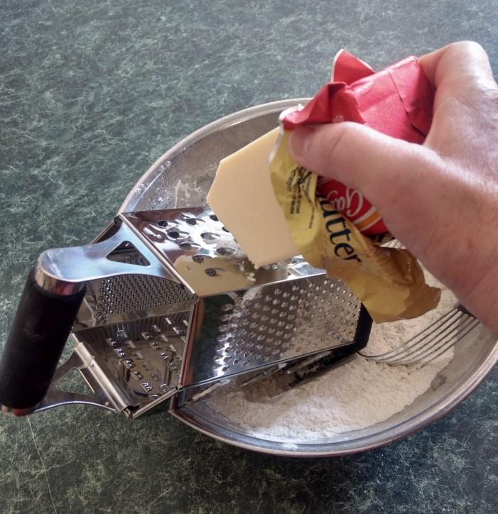Grating the frozen butter.