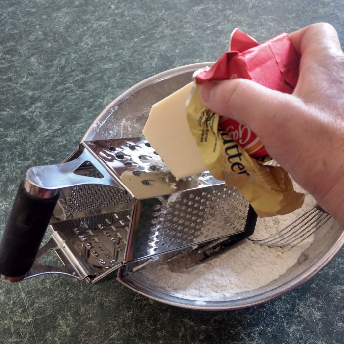 Grating the frozen butter.